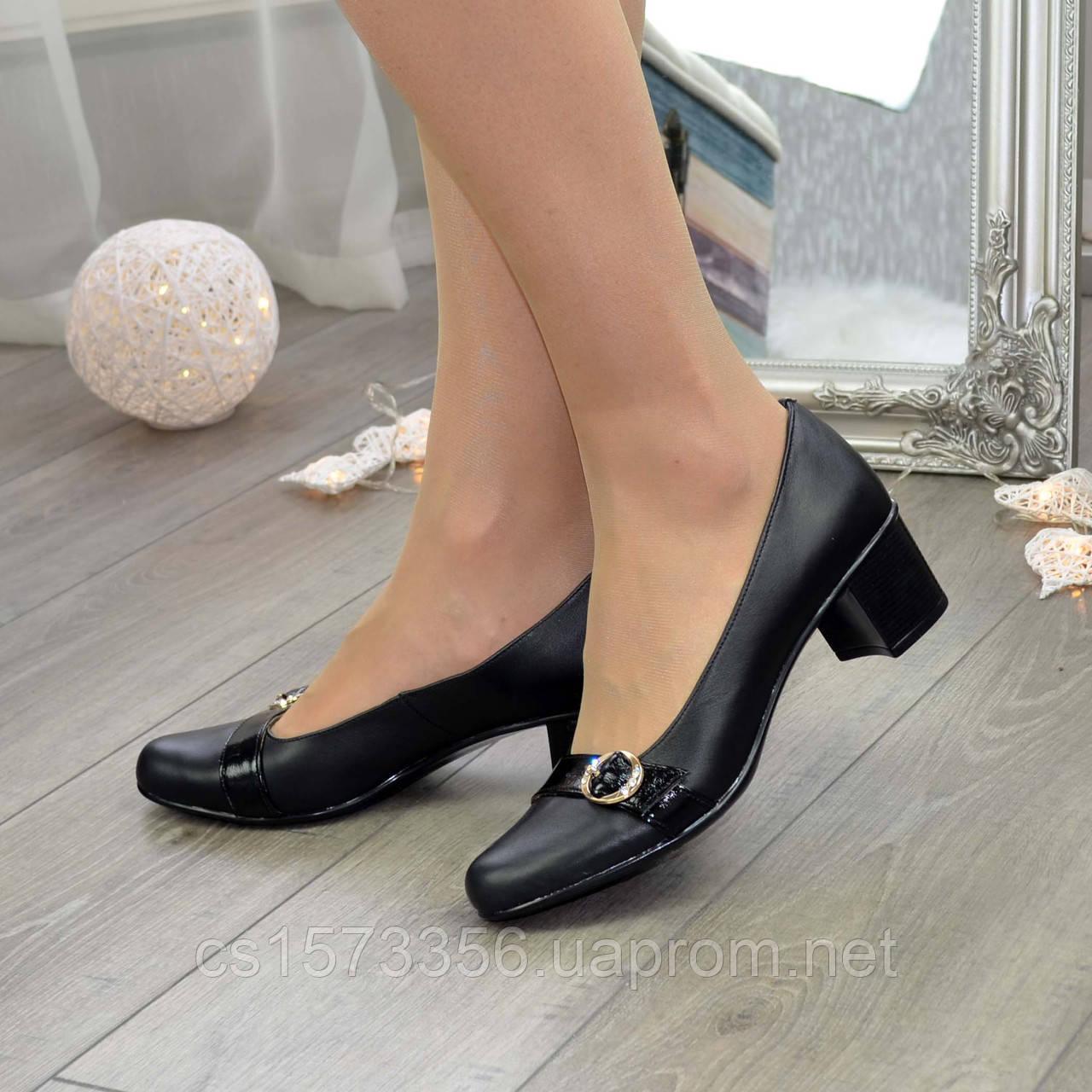 Женские кожаные туфли на невысоком каблуке декорированы брошкой.
