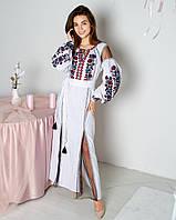 Красиве нарядне біле плаття в підлогу з стильною яскравою вишивкою
