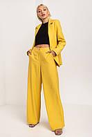 Яркий и стильный женский брючный костюм с пиджаком цвета шафран