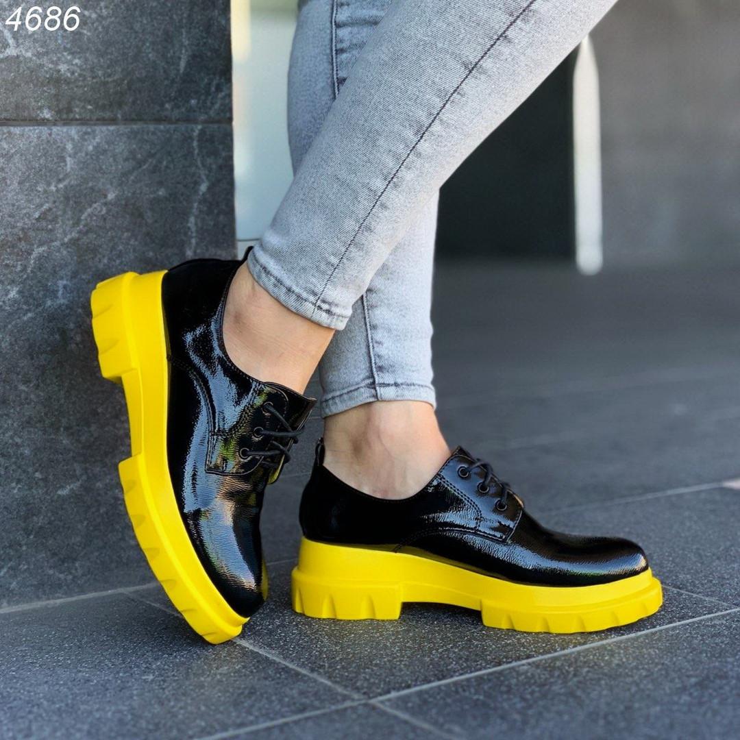 Закрытые черные лаковые туфли на желтой подошве