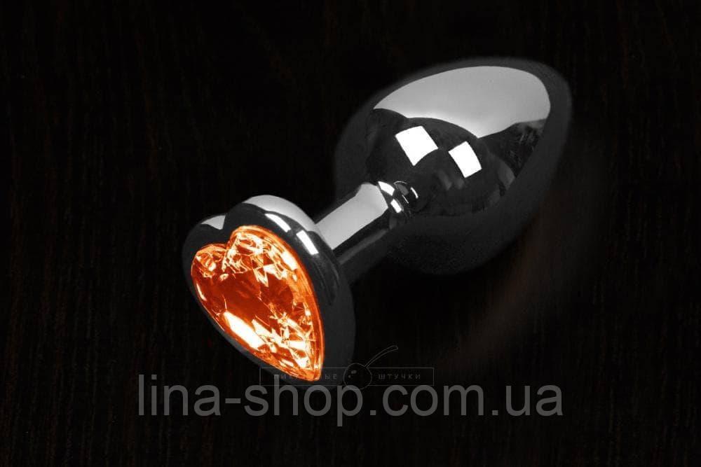 Пикантные Штучки Большая серебристая анальная пробка с кристаллом в виде сердечка 8,5Х4 см (оранжевый)