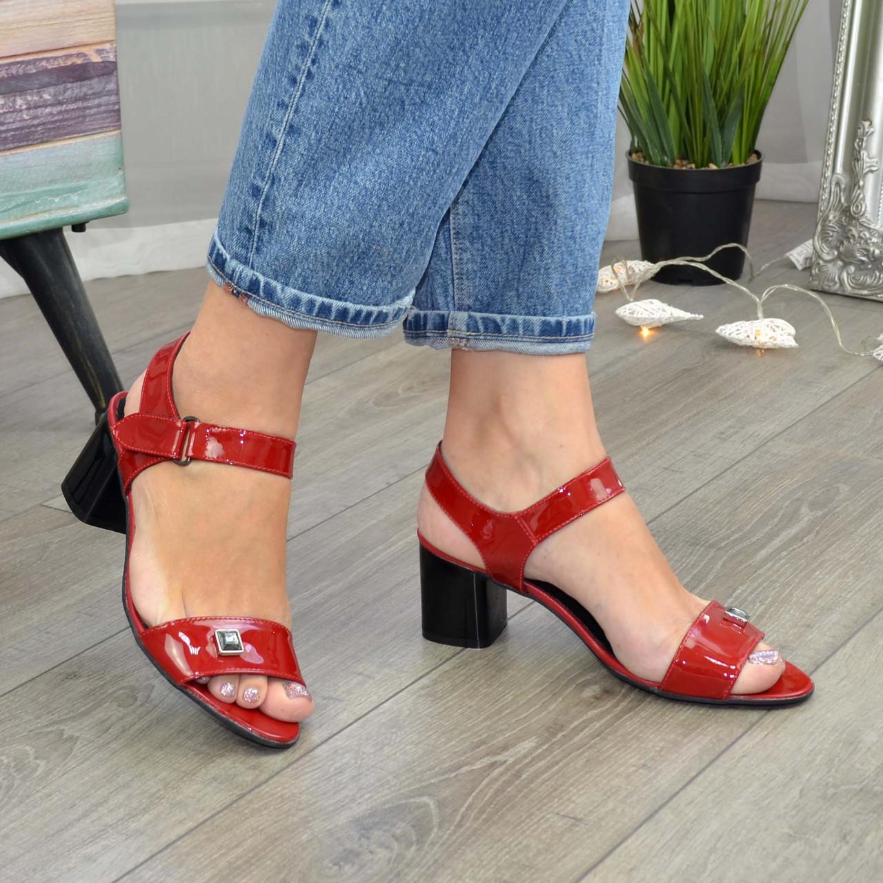 Женские лаковые красные босоножки на невысоком каблуке, декорированы фурнитурой.