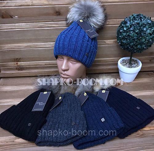 Детская зимняя вязанная шапка на флисе с натуральным бубоном енота оптом