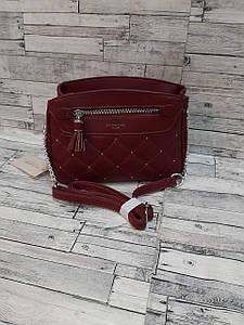 Стильная женская сумка красного цвета с клепками и кисточкой 23*17 см