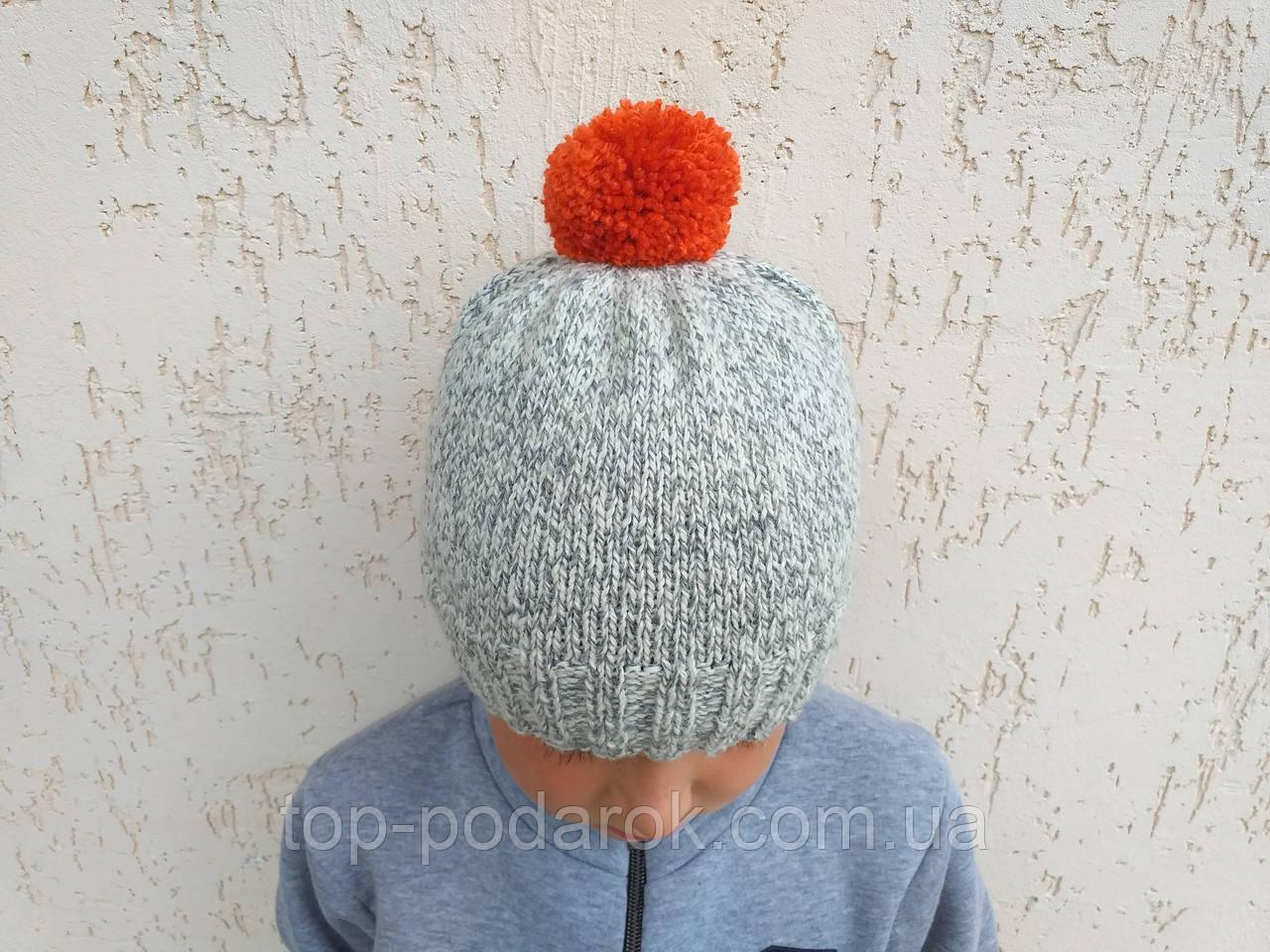 Серая вязанная шапка ручной работы с оранжевым помпоном