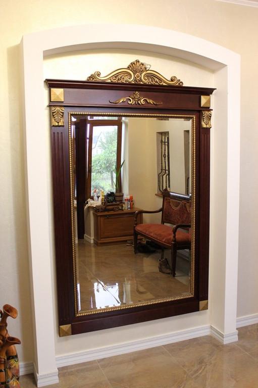 Зеркало с резными элементами на деревянной раме прекрасно смотрится в интерьере.