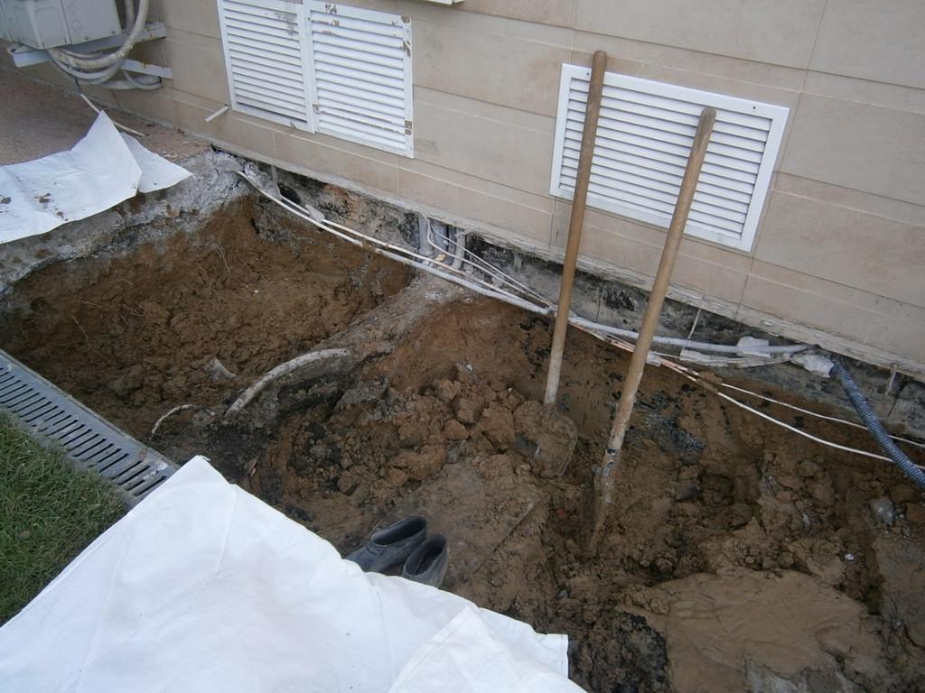 На этой фотографии изображено изъятие полностью замоченного глиняного замка из-под демонтированной бетонной отмостки. Глина выносилась на расстояние 60-70 метров за пределы участка и грузилась на самосвалы с последующим вывозом на свалку.