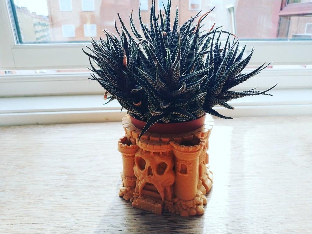 Ємність для рослин у вигляді замку