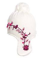Белая вязаная шапочка на флисе, украшенная бусинами.