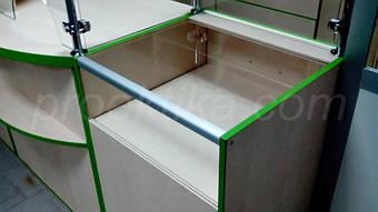 Прилавок с прозрачной столешницей на основе конструкции из ДСП, алюминиевого профиля и стекла.