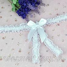 Откровенные трусики украшены кружевом и бантиком с разрезом для игр белого цвета