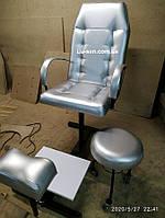 Серебристое педикюрное кресло с подставкой для ног и стулом для мастера.
