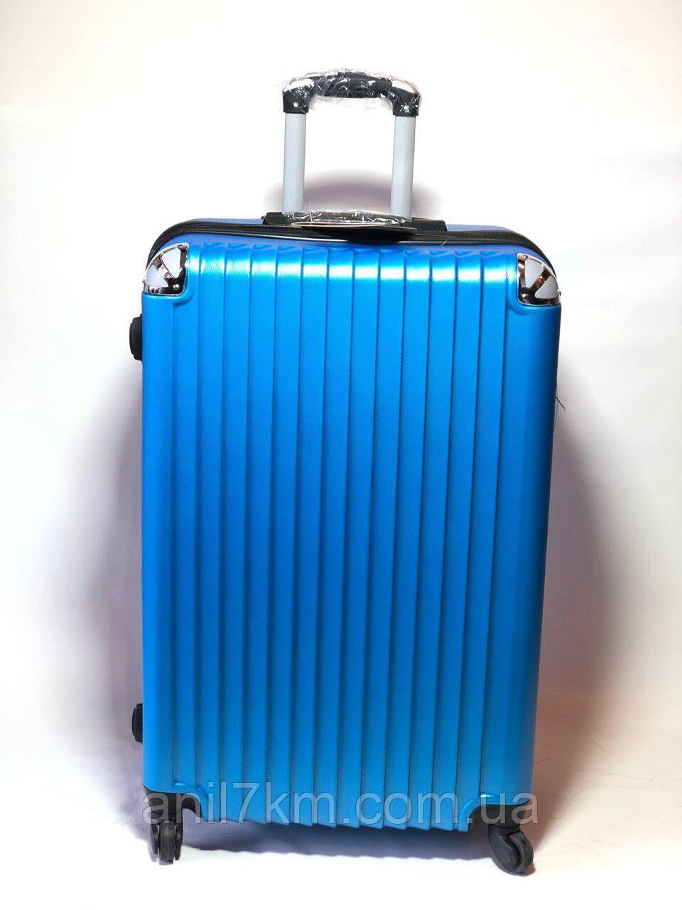Великий пластиковий чемодан на чотирьох колесах
