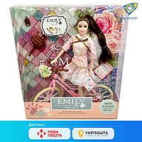 Кукла Эмили на велосипеде. Кукла с длинными волосами. Кукла шарнирная с цветами на велосипеде