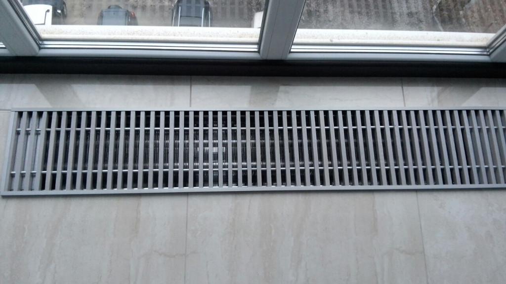 Деревянная решетка для внутрипольного конвектора окрашена под металлическую.