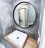Круглое зеркало в черной раме тонкой металлической