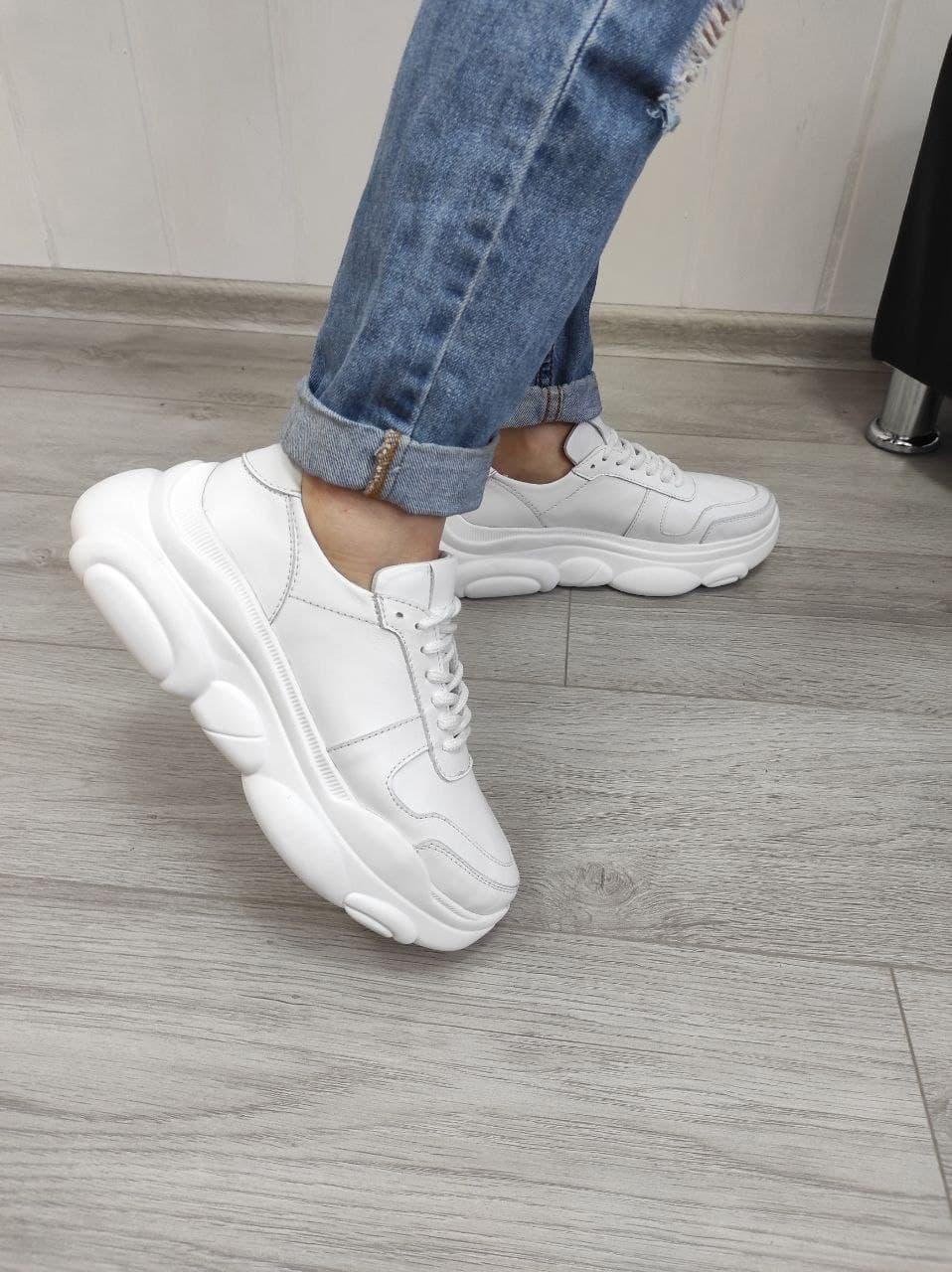 Білі шкіряні кросівки на підошві стильною