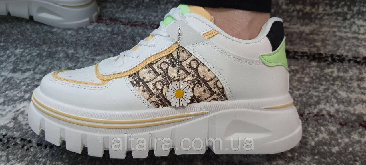 Стильні білі жіночі кросівки з буквеним принтом на високій підошві.