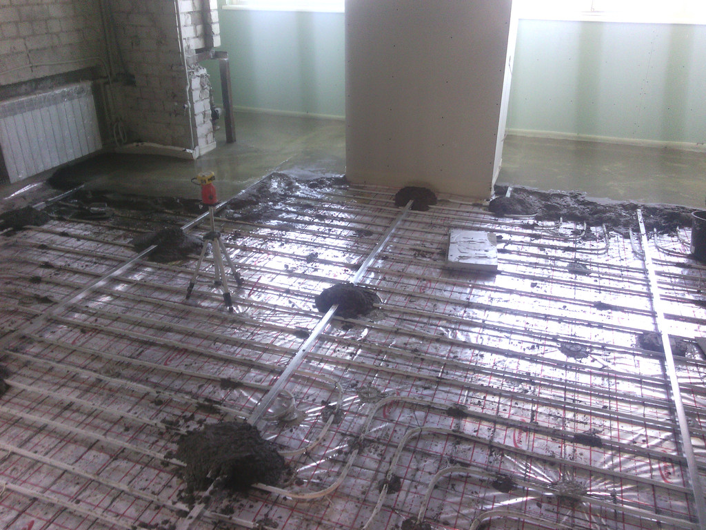 Стяжка по тёплому полу. Было увязана кладочная сетка, демпферная лента, установлены маяки, изготовлен на месте и уложен раствор (11-й этаж).