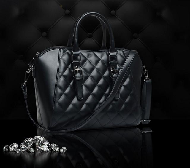Женская черная сумка через плечо на черном фоне.