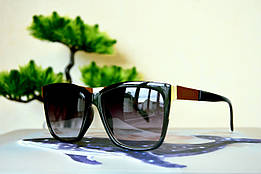 Солнцезащитные очки в черной с золотом оправе