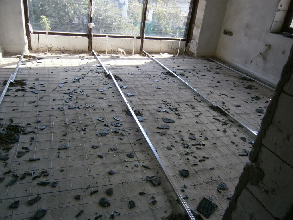 Чтобы армирующая сетка находилась не в самом низу слоя стяжки, с помощью битого кафеля она была частично приподнята на необходимую высоту
