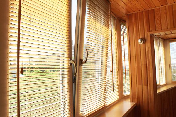 Завершенность балкону придают жалюзи из натурального дерева.