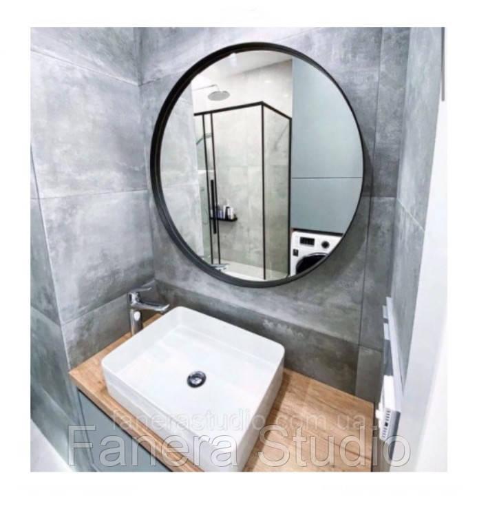Кругле дзеркало в чорній тонкій металевій рамі