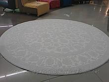 Круглий килим із білим малюнком на білому тлі