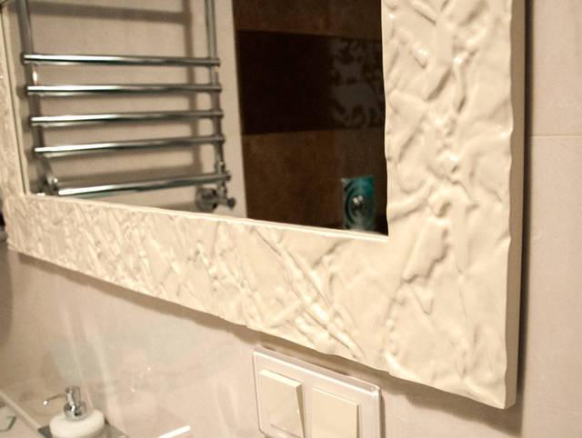 Зеркало в белом резном багете из дерева. Рисунок зеркала напоминает мятую бумагу.