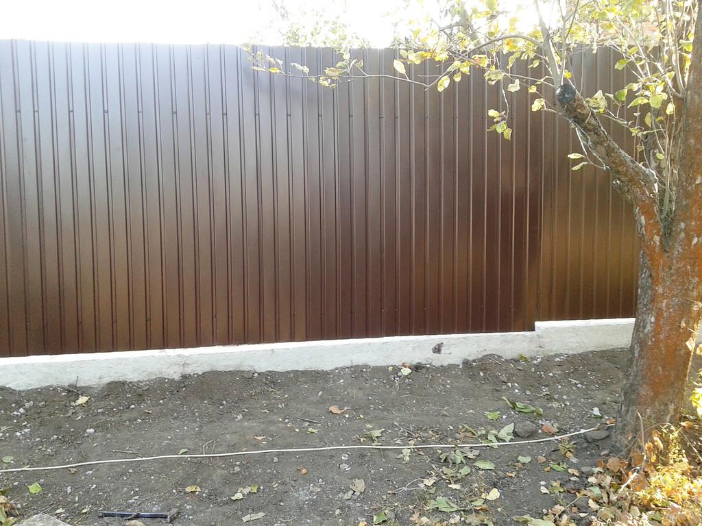 На сваренный металлокаркас из профильных труб прикручены листы профнастила, в данном случае - ПС-10, цвет 8017 (шоколад, глянец)