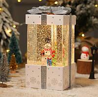 "Новогодний декор лампа -""Подарок"" со снегом и снеговиком белого цвета 18*10*10 см."