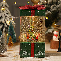 """Новогодний декор лампа -""""Подарок"""" со снегом и елкой зеленого цвета 18*10*10 см."""