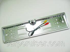 В рамке номерного знака камера заднего вида автомобиля  с белой подсветкой, с разметкой зоны приближения