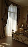 Шторы в спальню. Золотые бархатные портьеры украшены жестким и мягкими ламбрекенами с вышивкой и отделкой в виде принтованого черного бархата. В качестве подхватов используются золотые кисти и розетки. Легкий тюль мягко рассеивает солнечный свет.