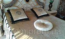 Золотое бархатное покрывало и подушки украшены черным бархатом, бахромой и вышивкой Версаче. В комнате достаточно солнечно и золотое оформление комнаты выглядит нарядно, светло и уютно.