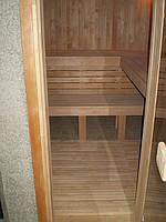 Вход в сауну. На кафельном полу лежит съёмный деревянный трапик. Торец нижней полки не зашивается брусом до пола, оставляется пространство между нижней полкой и полом для уборки и просушки сауны.