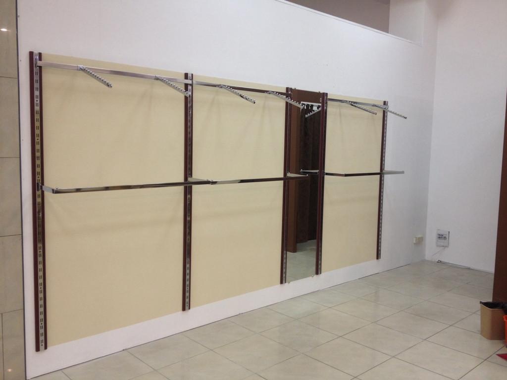 На этой фотографии, вы видите классическое торговое оборудование для магазина одежды состоящее из реек с деревянных декором и закрепленными на них перемычками с кронштейнами (вешало для одежды) и внизу дуги для плечиков.