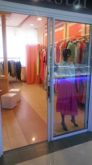 На витрине женский манекен черный лак, далее справа стойка для одежды настенная и примерочная для посетителей, по центру стойка для одежды остров и пуфики белого цвета квадратные.