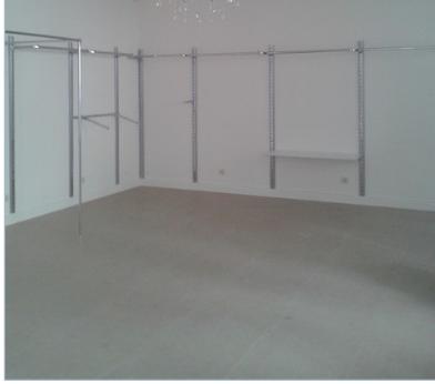 На этой фотографии, наш клиент собирает настенные стойки для одежды. По периметру закреплена на стену рейка и на нее навешано остальное торговое оборудование: дуги, перемычки, вешала, полкодержатели и примерочная в форме квадрата.