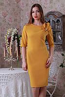 Стильное облегающее платье прямого силуэта с оригинальным декоративным элементом и золотистой брошью.