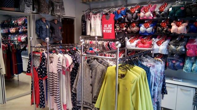 На этом фото мы видим по центру стойку для магазина одежды двойную и плечики с товаром. По периметру слева направо: торсы манекены женские и далее стойку для одежды настенную укомплектованную рейками и перемычками на которые закреплены вешала.