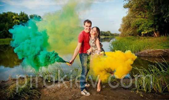 зелёный и желтый дым в руках у парня и девушки. Фотосессия с цветным дымом на природе