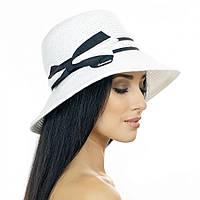 Мини-шляпка белого цвета с черно-белым бантом.