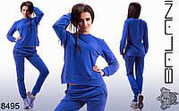 Женский однотонный спортивный костюм: асимметричный батник и брюки.