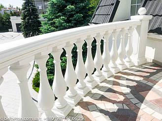 Белая балюстрада с квадратными тумбами ограждает террасу над входной группой