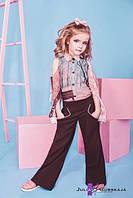 Расклешенные от линии бедра детские брюки с геометрическими карманами спереди.