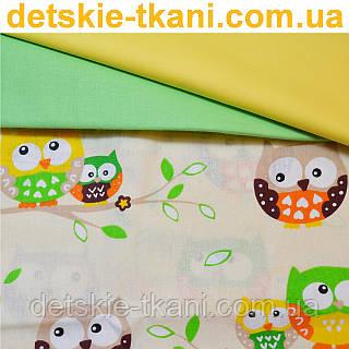 Ткань с салатовыми совушками на бежевом фоне.