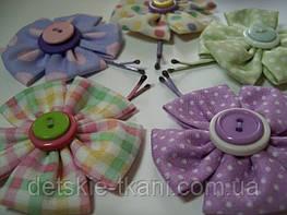 Заколки с цветами из ткани могут удачно дополнить гардероб малышки.