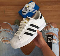 Женские кроссовки Adidas Superstar, белые с черными полосками.